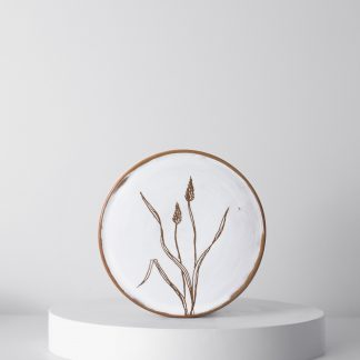 A Wildflower plate showing handcarved botanics on a handthrown plate, by Gallery Nordeinde
